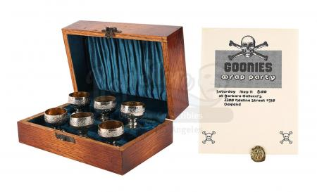Lot #308 - THE GOONIES (1985) - Treasure Coin, Goblet Set and Wrap Party Invitation